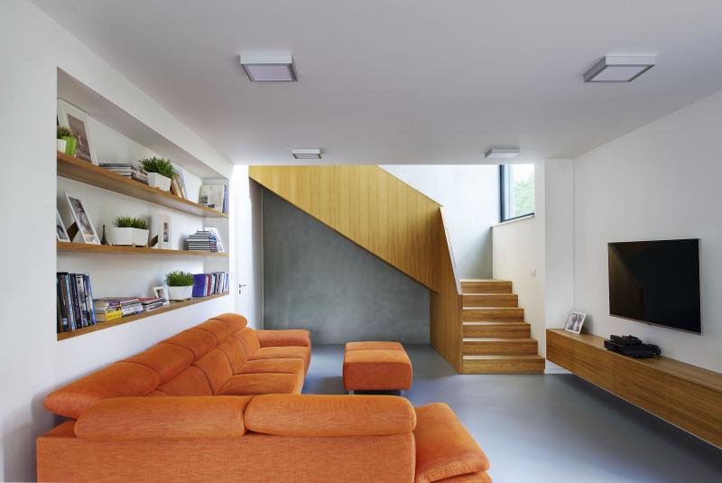 Šedá fasáda z masivní části domu se promítá i na stěně u dubového schodiště. Opticky tak odděluje dřevostavbu od zděné části domu. Barvy a vybavení byly vybrány velmi pečlivě, dbalo se na každý detail zpracování