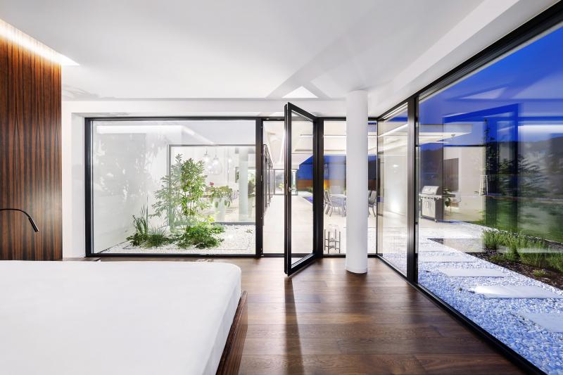 Volný průhled z ložnice přes atrium, společný obývací prostor a druhé atrium až do relaxační místnosti odhaluje základní koncept domu