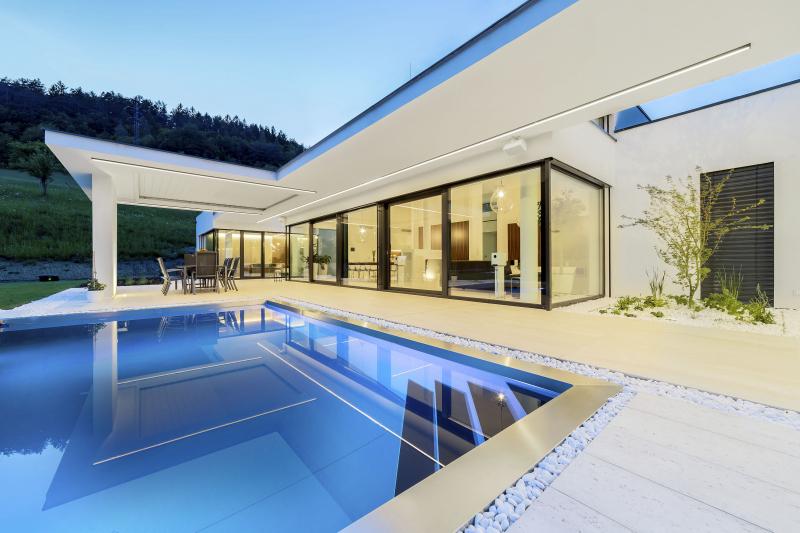 """Tvar domu vynikne zejména večer. Všechny železobetonové moniéry jsou opatřeny přisazenými liniemi LED osvětlení, které je opticky """"povznášejí"""" nad terénem a zvýrazňují horizontálu samotné stavby domu. V rozšířené části terasy je moniéra podepřena železobetonovou stěnou. Nad jídelním stolem bylo instalováno stínění z plastových lamel, které lze naklápět podle směru slunečních paprsků nebo z cela shrnout do strany"""