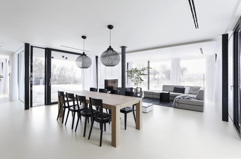 Hodně skla a kontrast černé a bílé vládnou i uvnitř domu. Osvětlení je kombinováno převážně z nabídky českého výrobce Halla (LED svítidla), společnému obývacímu prostoru kralují drátěné lustry značky Moooi nad jídelním stolem