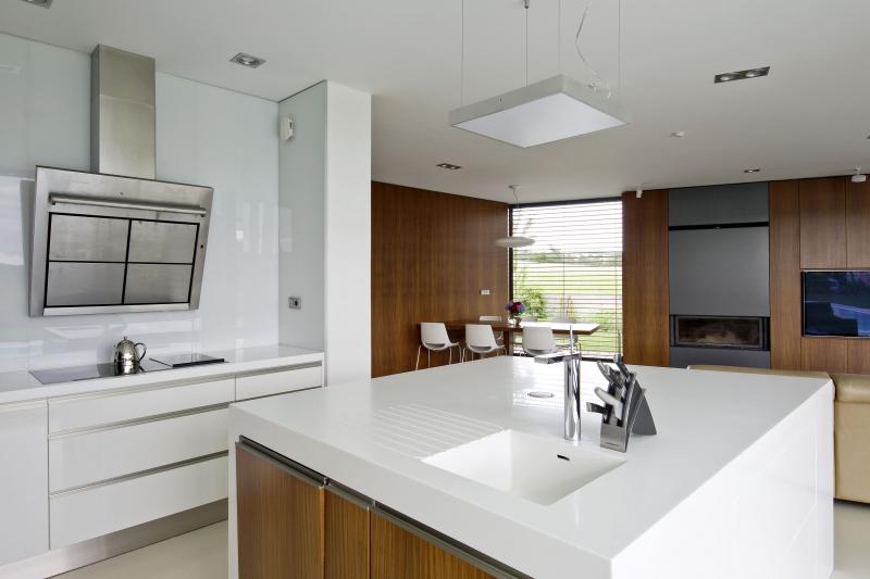Čtvercový kuchyňský ostrůvek s pracovní deskou a bočnicí z Corianu tvoří atraktivní prostorový předěl a je také velmi praktický