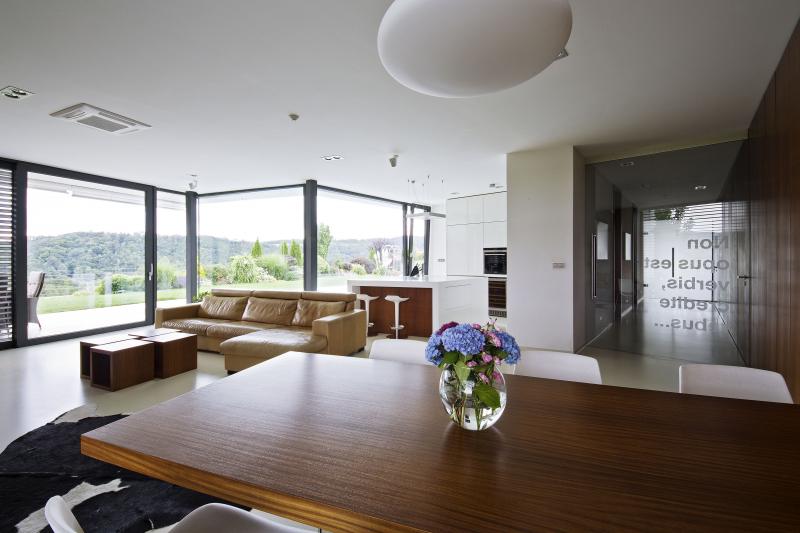 Společným jmenovatelem obytných místností je krásný výhled. Aby zůstal zachován velký otevřený vnitřní prostor a přímý kontakt se zahradou, je použito velkoplošné zasklení (zčásti se skrytými rámy) a strop u prosklené stěny podporují subtilní ocelové sloupky