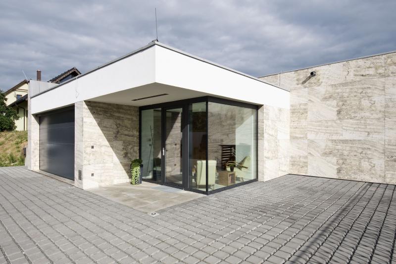 Hlavní vstup do domu je chráněn velkým krytým závětřím. Prosklené stěny a vstupní dveře přivádějí do šatny a chodby hodně světla a vytvářejí při příchodu pozitivní dojem
