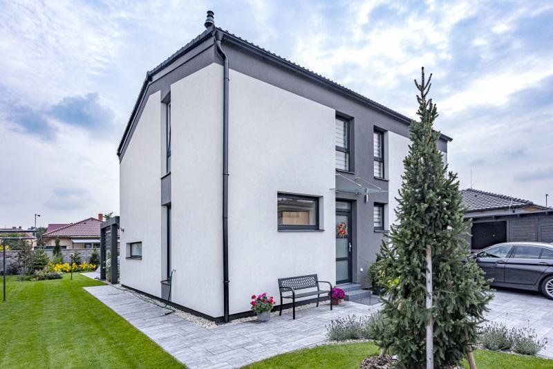 Vstupní partie domu působí přívětivě, stejně jako celý interiér. Zajímavá jsou vysoká vertikální okna v patře, dělená na spodní pevnou a horní otevíravou část. Toto řešení přináší více bezpečí a je velmi praktické
