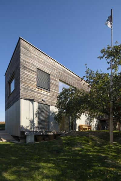 Plášť domu tvoří povrchově neošetřená modřínová prkna kladená horizontálně, která postupem času získávají přirozenou patinu. Ve spodní části stavby jsou doplněna fasádními deskami Cembrit