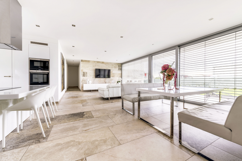 Společenskému prostoru dominuje bílá kožená souprava (Natuzzi), bílá komoda (Hanák nábytek) a velkoformátová dlažba imitující travertin, která přechází z podlahy částečně na stěnu a posléze i do exteriéru