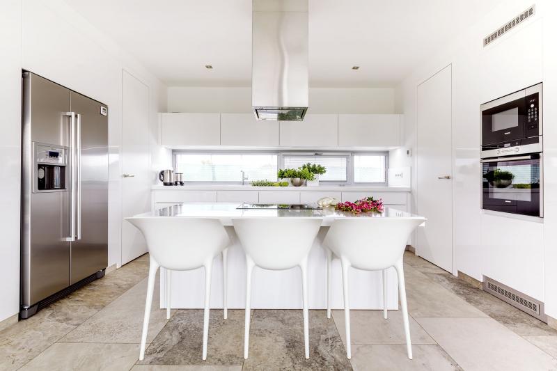 Běloskvoucí dojem interiéru umocňuje bílý nábytek, například polykarbonátové židle Dr. Yes designéra Philippe Starcka a podle Kamilina návrhu na míru zhotovená kuchyň z MDF desky lakované do vysokého lesku