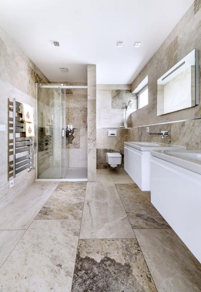 Koupelna rodičů je kompletně obložena velkoformátovou dlažbou (Impronta) imitující travertin a vybavena dvěma umyvadly Palomba (Laufen) s bateriemi Hansgrohe
