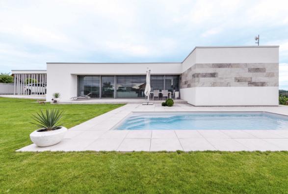 Celý dům září bělobou. Efektně kontrastuje se svěží zelení úhledného trávníku a azurově modrým bazénem