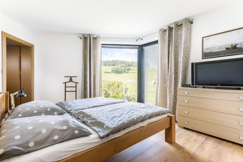 Ani v ložnici nechybí kouzelný výhled. Nároží je záměrně zkosené a rohovým oknem lze přímo z postele sledovat, jak si ranní paprsky slunce razí cestu mezi protilehlými k opci