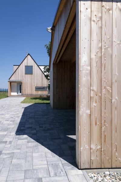 Garážové stání a dům jsou architektonicky sladěny a propojeny betonovou zámkovou dlažbou. Hlavní vchodové dveře jsou chráněny dřevěným závětřím