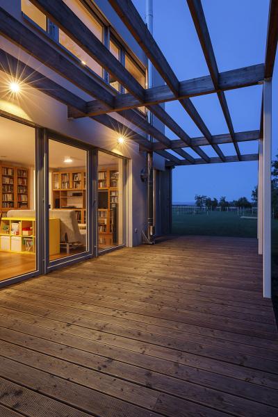 Úroveň podlahy a terasy je zvýšena o 300 mm nad terénem. Zastínění zajišťuje lehká pergola ze subtilních lepených dřevěných profilů