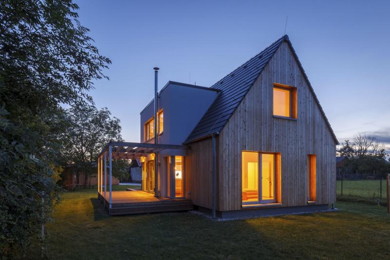 K domu se z jižní strany připojuje dřevěná paluba s pergolou ze subtilních lepených dřevěných hranolů