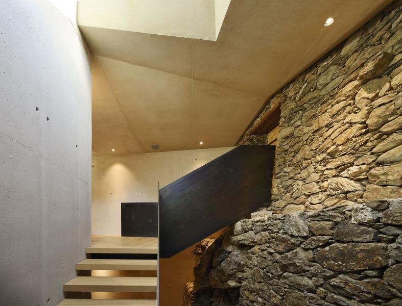 V hale spojující starou a novou stavbu zůstalo záměrně odkryté historické kamenné zdivo, aby vyprávělo historii místa a vytvářelo kontinuitu