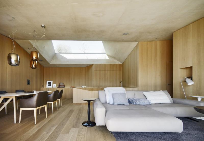 Vybavení interiéru, podlahy a obložení stěn byly vyrobeny na zakázku z přírodního dřeva ze zdejších lesů. Bezzárubňové dveře, jednoduchá kuchyňská linka a velké hladké plochy vytvářejí kompaktní monolitický tvar, který je doplněn zajímavými svítidly a nábytkovými solitéry