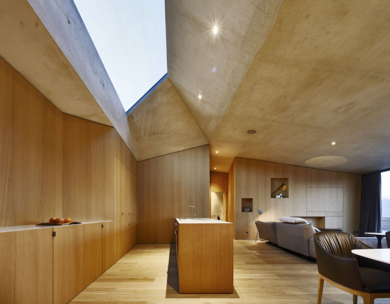 """Téměř veškeré vybavení interiéru je koncipováno jako vestavěné. Obložení stěn """"maskuje"""" integrované skříně a další úložné prostory, pro oživení zde architekt vytvořil zajímavé niky"""