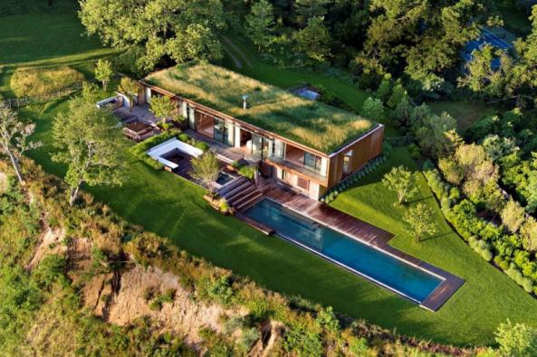 Dům působí dojmem, že vyrostl ze země přímo pod mohutnými platany a žije a dýchá s okolní přírodou