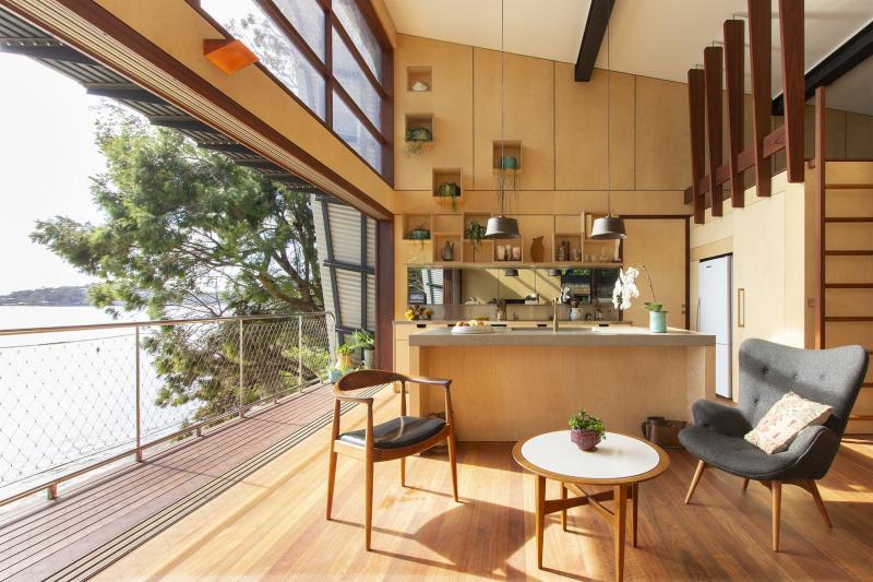 Obývací pokoj bezbariérově přechází v balkon. Na dřevěný decking je osazeno zábradlí z odolných nerezových trubek a pletiva