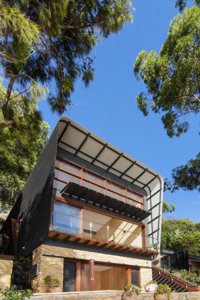 """Horní podlaží je ukryto pod kompaktním obalem z vlnitého hliníkového plechu. """"Inspirovali jsme se obaly z vlnité lepenky,"""" říká architekt Rob Brown. Na hlavní pohledové straně plech přesahuje přes fasádu a plní funkci kšiltu na ochranu před větrem, sluncem a deštěm. Protože prosklená plocha je vysoká přes 2 podlaží, zavěsili architekti na fasádu ve výšce 3 metry ještě slunolam z ocelových profilů"""