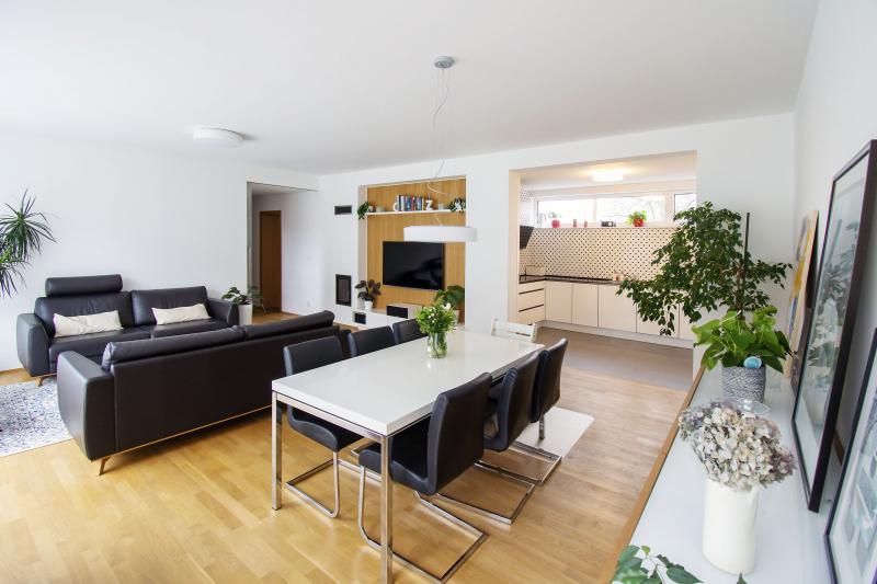 Hlavní obytný prostor spojuje obývací pokoj, jídelnu a kuchyni. Díky vhodné kombinaci dřeva s černou kůží, chromovými prvky a bílými plochami pokoj působí domácky, ale přitom elegantně