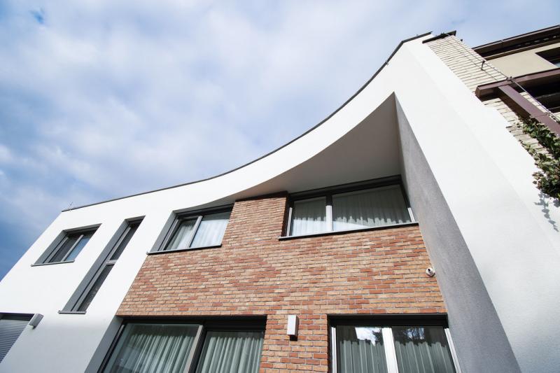 Jednoduchý design domu ozvláštňuje cihlový páskový obklad a zakřivený přesah střechy, který srovnává linii fasády se sousedním domem