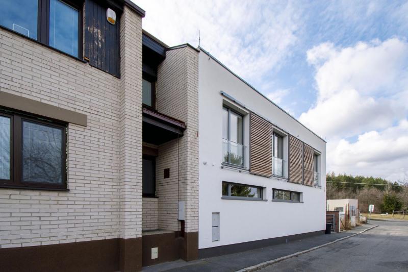 Směrem do ulice má dům hladkou bílou fasádu. Horizontální okna v přízemí jsou umístěna vysoko, aby do interiéru nebylo vidět, okna v patře lze zakrýt posuvnými stínicími prvky z dřevěných lamel