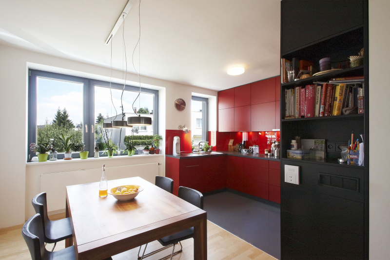 Kuchyňský kout ve tvaru písmene U o rozměrech 120 x 360 cm je využit na maximum, úložné prostory sahají až do stropu. Nová okna jsou dřevěná, neutrální šedé rámy ladí jak s interiérem, tak s předokenními hliníkovými žaluziemi