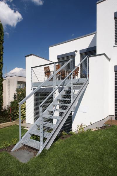 """Terasa v prvním patře """"chytá"""" jižní a západní slunce. Zábradlí a schodiště na zahradu, konstruované z válcovaných ocelových profilů, pororoštů, jeklů a ocelových lanek dávají domu industriální ráz"""