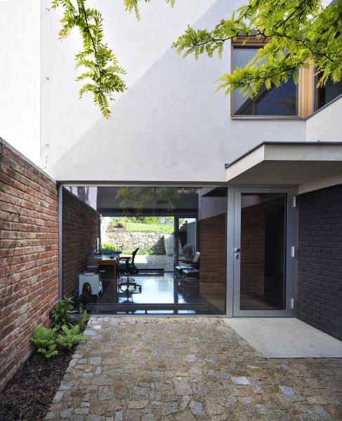 Atrium je vydlážděno žulovou dlažbou. Volný průhled přes prosklený ateliér až na zahradu za domem opticky odlehčuje hmotu domu a zvětšuje prostor