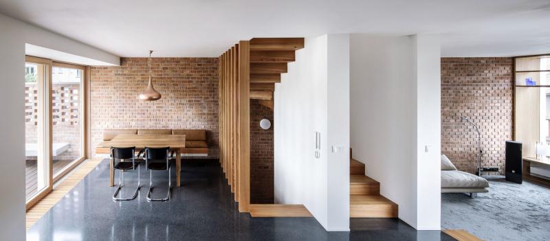 Schodiště volně odděluje relaxační část od kuchyně s jídelním koutem. Oddělení se promítá i na podlaze rozdělené na bavlněný koberec a hladkou plochu z litého terazza antracitové barvy. Celá štítová stěna je obezděna režnými cihlami, tato nekonečná struktura vnáší do interiéru příjemnou nepravidelnost a pokračuje ven do exteriéru