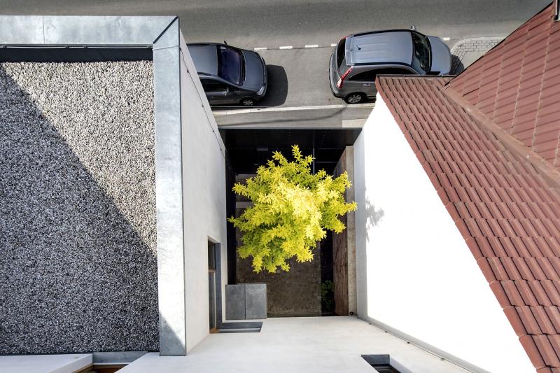 Část domu ustupuje směrem do zahrady, což uvolnilo místo pro malé atrium, uzavřené ze tří stran zdmi a z ulice vysokou bránou z černého ocelového plechu. Vznikl tak příjemně chráněný parter se zelenou dominantou (dřezovec trojtrnný)