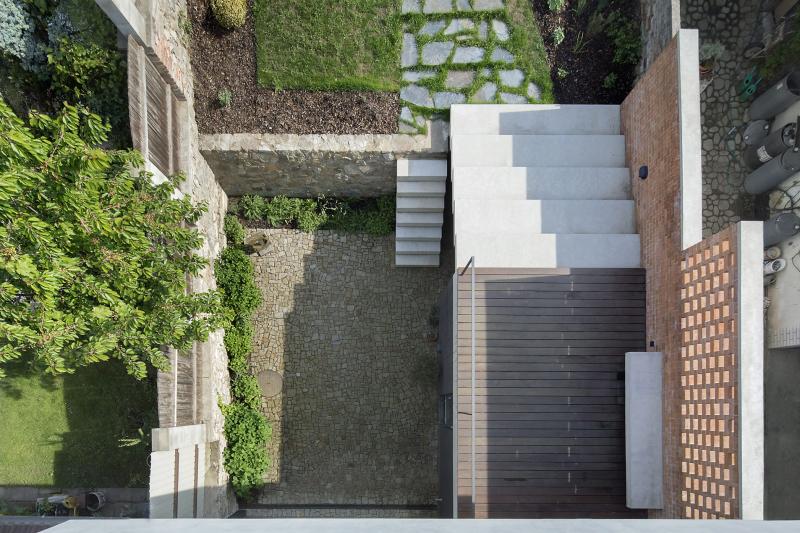 Terasy a zahradu propojují dvě venkovní betonová schodiště. Architekti si nápaditě pohráli s režným cihelným zdivem. Dělicí zídka z klasických plných cihel obsahuje zavěšenou betonovou lavičku, děrovaná horní část propouští světlo a vytváří zajímavou a proměnlivou hru světla a stínů