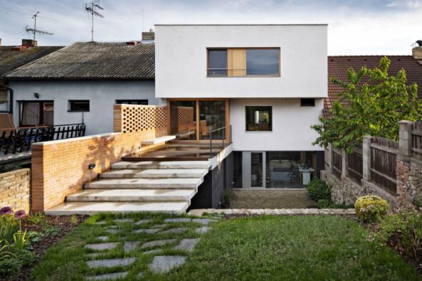 Ze zahrady je dům třípodlažní. Z hlavního obývacího prostoru vede výstup na malou dřevěnou terasu, pod níž se nachází zázemí a schůdky do původního sklípku. Ateliér má vlastní terasu – dvorek vydlážděný žulovými odštěpky a kostkami. Přízemí je barevně odlišeno od horní obytné části – režné cihly na fasádě jsou opatřeny černým nátěrem, okna mají rámy z eloxovaného hliníku