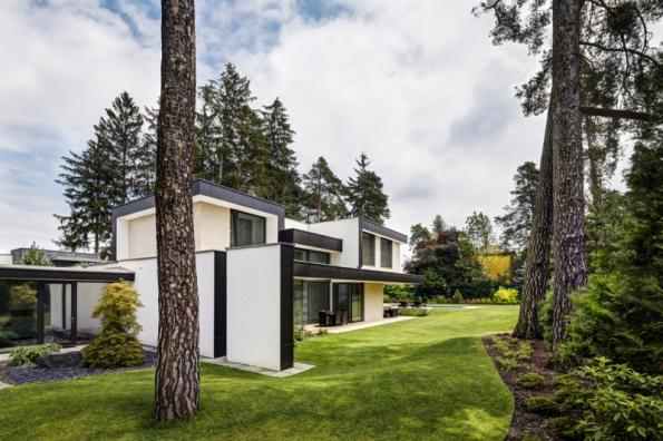 Tento dům vznikl prakticky v lese, umístění i návrh byly promyšleny tak, aby na pozemku zůstaly staré borovice. Ty mimo jiné vytvářejí příjemné přirozeně vlhké a stinné klima