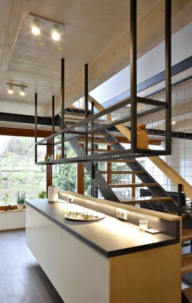 Řešení kuchyně je zcela jednoduché, dvě linky naproti sobě, jedna s horními skříňkami a zabudovanou lednicí a skříní na potraviny. Druhá s pultem směrem ke schodišti a shora svěšenou kovovou policí, která souzní s řešením schodiště