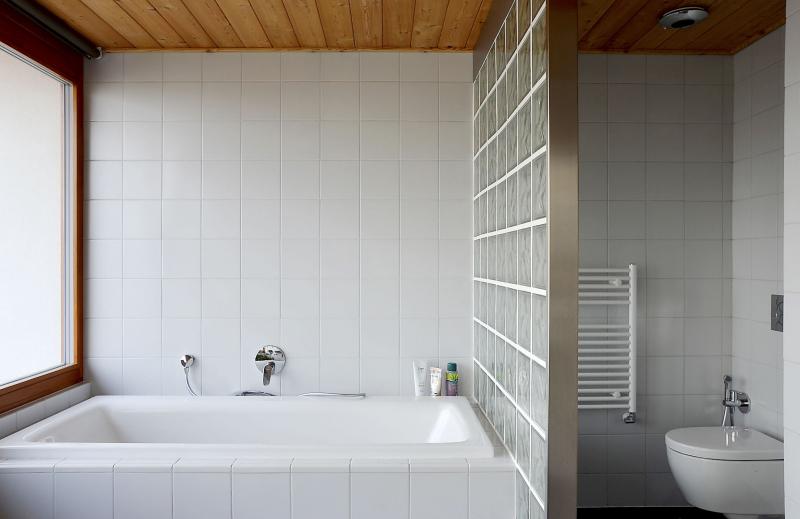 Koupelna získala lázeňský charakter, nikoli však ve smyslu luxusního pojetí. V tradičních lázních se používalo až spartánské vybavení – bílé obkladačky, v tomto případě také luxfery a modřínové dřevo na stropě. Střídmé je také základní vybavení pobytové haly v patře