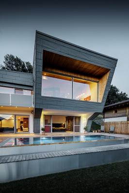Vilu zasazenou vkopci nad rakouským Dölsachem nedaleko Lienzu jen tak nepřehlédnete. Pozornost upoutá čistými geometrickými liniemi, dominantní prosklenou stěnou, zajímavě řešenou střechou a fasádou odrážející světlo. Majestátní vrcholy Dolomit jsou odsud jako na dlani. Architekt, který se podepsal pod návrh této stavby, totiž zdejší hory miluje. Stejně jako preciznost a rozmanité výzvy. Ty jdou vsoučasné době ruku vruce se stále vyššími požadavky klientů na udržitelnost a ekologický ráz domů. (Zdroj: PREFA)