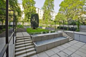Původní zahrada byla ostře rozdělená na spodní zpevněnou část (dvoreček) a horní zatravněnou část, které byly odděleny úzkým schodištěm a vysokou terénní zdí. Zahrada byla přístupná pouze ze suterénu. Návrh vytvořil nové terasy, které úrovňově propojují přízemní byty s horní částí zahrady a vytváří nové vstupy do zahrady. Původně stísněná spodní část zahrady se více otevřela díky pozvolnému výškovému přechodu do horní zahrady dvouramenným schodištěm a dvojúrovňovým vodním prvkem