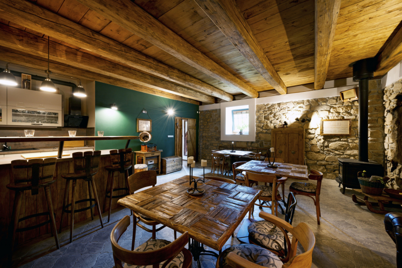 Přízemí slouží k relaxaci a setkávání s přáteli. Společenská místnost má díky původním dřevěným stropům a kamennému zdivu působivou atmosféru. Z vyřazených starých trámů byly vyrobeny originální stoly a další nábytek. Autentického ducha má i dlažba a dveře, připomínající dvířka do stájí