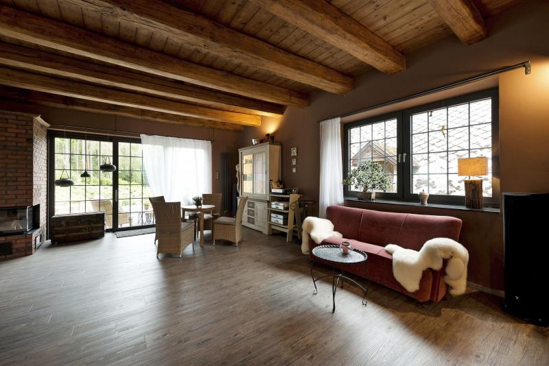 Bývalá mlýnice se proměnila ve velkorysý společný obývací prostor vybavený rohovým krbem a stylovým nábytkem. I zde má hlavní roli dřevo, především původní trámový strop