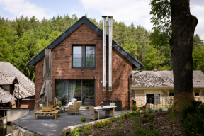 Dům navazuje na svah, proto je společný obývací prostor umístěn v patře, aby mohl být propojen s terasou. Obklad fasády z cihelných pásků, přiznané nerezové komíny a antracitová tabulková okna prozrazují zálibu majitelů v industriálním stylu