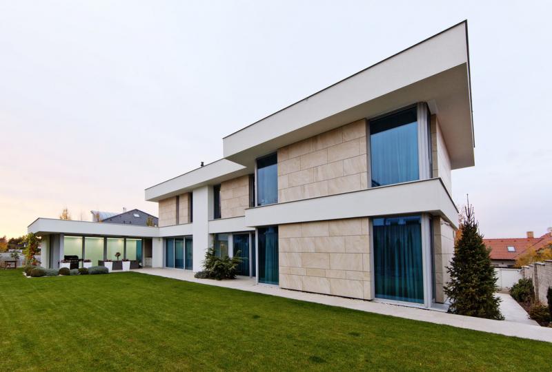 Kompozici domu tvoří dvě navzájem posunuté dvoupodlažní hmoty a přízemní bazén. Propojují je horizontální pásy bílé omítky, jakési variace na tradiční římsy. Hladké plochy příjemně kontrastují se strukturou zavěšeného travertinového obkladu fasády