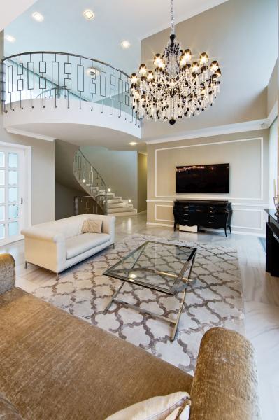 Dominantou společné obývací haly je kruhové schodiště s chromovaným zábradlím. Křišťálový lustr, dekorativní štuky a koberec s historizujícím vzorem, černá lakovaná komoda a další nábytek s neobarokními prvky jsou charakteristické pro tzv. glamour styl