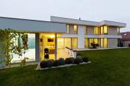 Prakticky všechny obytné místnosti i bazén jsou orientovány do klidové části zahrady. Těsnému propojení interiéru a exteriéru napomáhají okna na celou výšku podlaží a prosklené rohové plochy, které navíc dodávají maximum světla. Velká terasa a krytá venkovní kuchyně u bazénu jasně vypovídají o životním stylu rodiny
