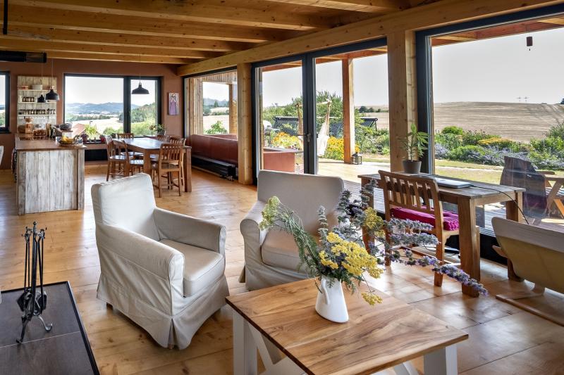 Také interiéru vládne přírodní dřevo. Na stěnách je kombinováno s hliněnými omítkami. V hlavním obývacím prostoru se, stejně jako v celém domě, uplatnily výhledy a výtvarné cítění majitelky domu