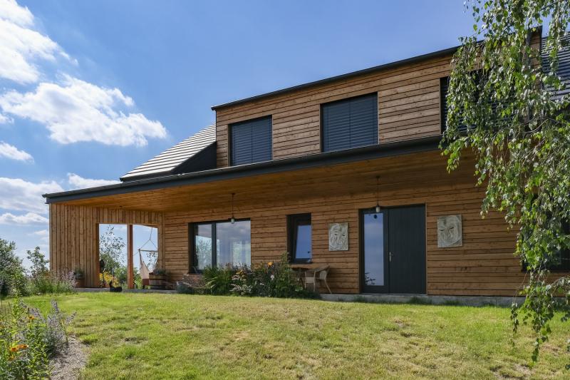 Fasáda má větraný obklad z modřínového dřeva, které časem získá přirozenou patinu. Jeho zbarvení kontrastuje s antracitovými okenními rámy, žaluziemi a černou taškovou krytinou