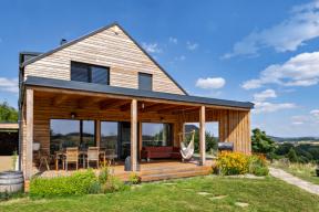 K nejoblíbenějším částem domu patří velká krytá terasa, využívaná jako venkovní obývací pokoj. Zajímavým prvkem je šikmá boční stěna s průchodem. Tvoří ochranu před sluncem a větrem, ale nebrání výhledu