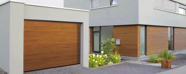Rolovací dveře RollMatic s designem dřeva můžete elegantně sjednotit s fasádním obkladem (HÖRMANN)