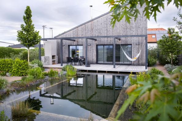 Vodní pokoj s jezerem a obývací pokoj jsou zcela propojené dřevěnou terasou, takříkajíc jsou mezi nimi zbořeny všechny pomyslné zdi. Než byste vytvářeli dva pokoje střední velikosti, raději postavte jeden pořádný, kde se snoubí veškeré pohodlí velkorysé terasy s efektem vodního prvku (atelier FLERA)