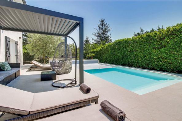 Dokonalé sladění bazénu s okolím je umožněno i díky tomu, že firma Desjoyaux vyrábí pro své bazény speciální betonovou dlažbu. Je protiskluzná a v létě se nepřehřívá (DESJOYAUX)
